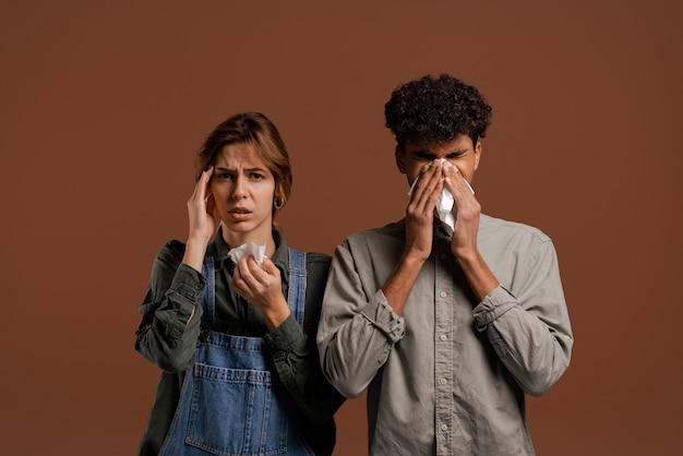 Foto van een schattig stel boeren, beiden snuiten hun neus en werden ziek. vrouw draagt denim overall, man draagt t-shirt geïsoleerde bruine kleur achtergrond.