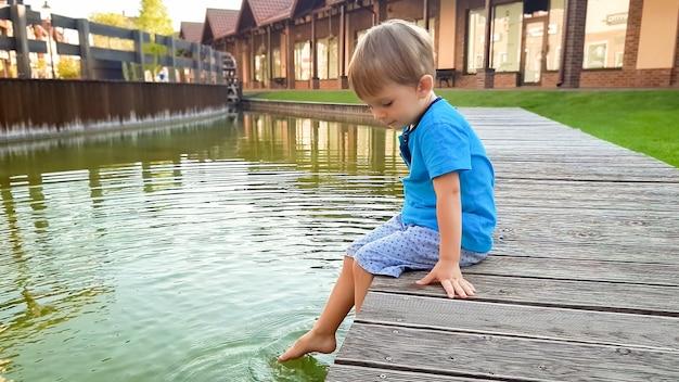 Foto van een schattige 3 jaar oude kleine jongen zittend op de rivieroever bij het waterkanaal in de oude stad en opspattend water met voeten.