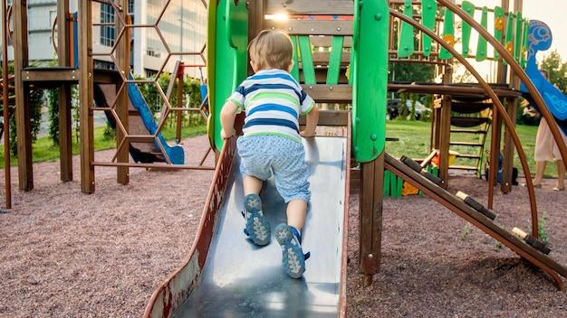 Foto van een schattige 3 jaar oude peuterjongen die klimt en rijdt op een grote glijbaan op de kinderspeelplaats in het park