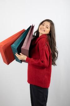 Foto van een schattige dame in een trui die haar boodschappentassen vasthoudt.