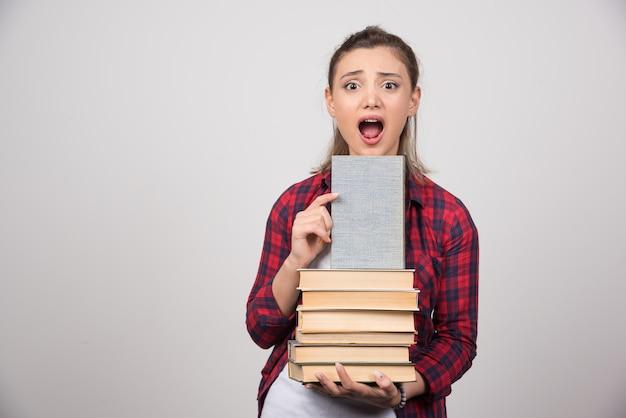 Foto van een schattige jonge student die een stapel boeken vasthoudt.