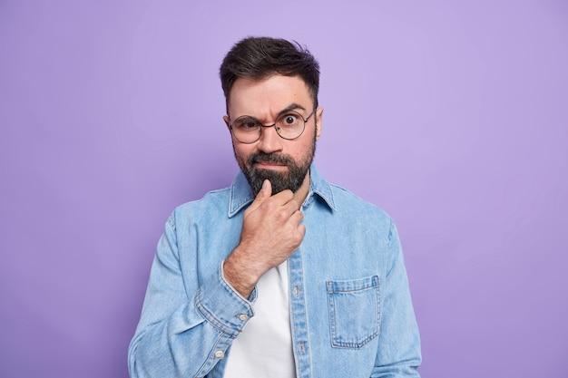 Foto van een serieuze, bebaarde volwassen man die zijn kin vasthoudt, zijn wenkbrauwen opheft en zijn gezicht gekleed in een modieus hemd dat ontevreden is met iets