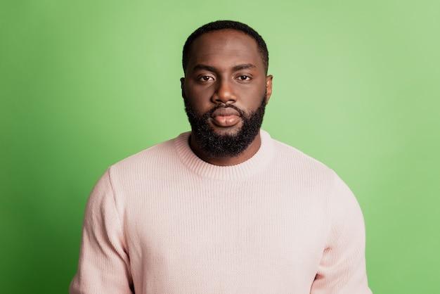 Foto van een serieuze, kalme afrikaanse man die op een camera gericht kijkt en een wit t-shirt draagt over een groene achtergrond