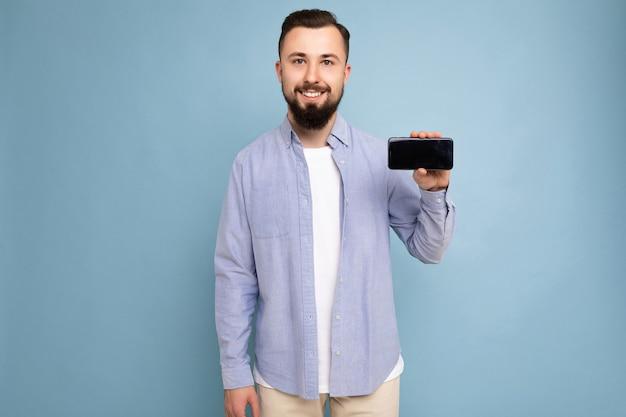 Foto van een serieuze knappe, knappe jonge brunette ongeschoren man met baard die casual wit draagt