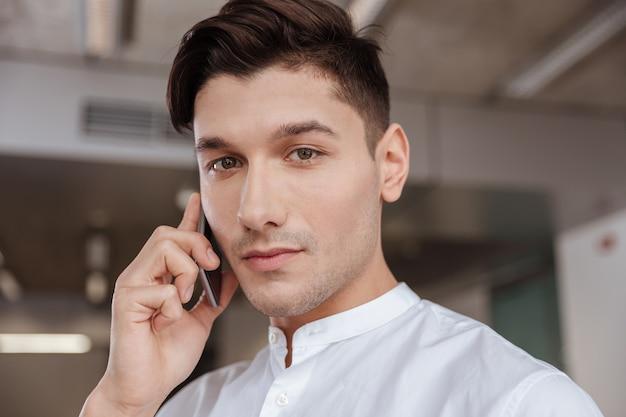 Foto van een serieuze man gekleed in een wit overhemd die binnenshuis aan de telefoon praat. samenwerken. camera kijken.
