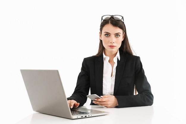 Foto van een serieuze vrouwelijke werkneemster, gekleed in formele kleding, zittend aan een bureau en werkend op een laptop op kantoor geïsoleerd over een witte muur