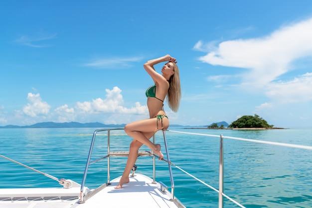 Foto van een sexy model poseren in een groene bikini in profiel zittend op de reling van een dure, luxe dek. rijke eigenaardigheden. reizen in de warme zeeën. mariene achtergrond.