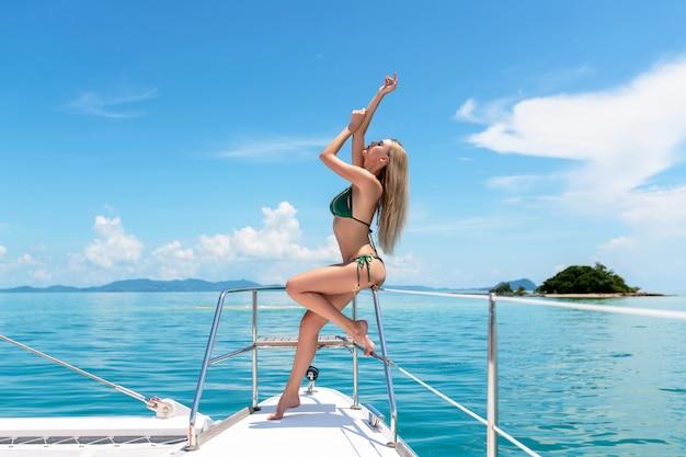 Foto van een sexy model poseren in een groene bikini in profiel zittend op de reling van een dure, luxe dek, waartegen een klein eiland is. reis op warme zeeën. mariene achtergrond.