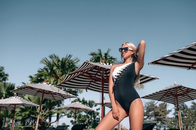 Foto van een slank blondje dat zwempak draagt en op het strand stelt