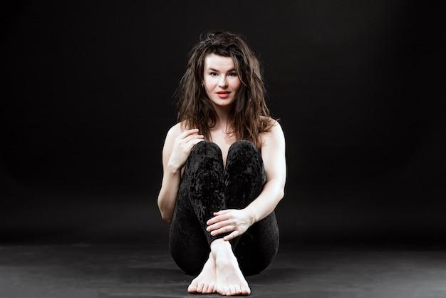 Foto van een soort gevoelige vrouwenzitting op de vloer op een zwarte achtergrond