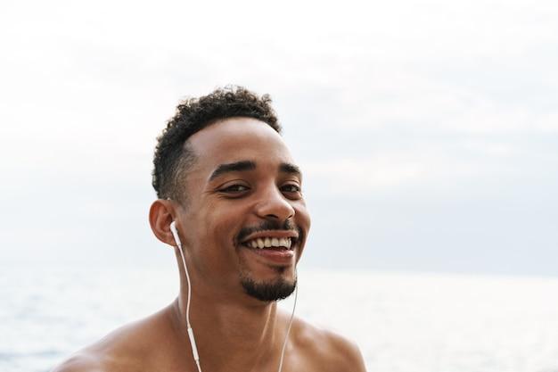 Foto van een sterke gelukkige knappe jonge afrikaanse sportman buiten aan het strand, zee, luisterende muziek met koptelefoon.