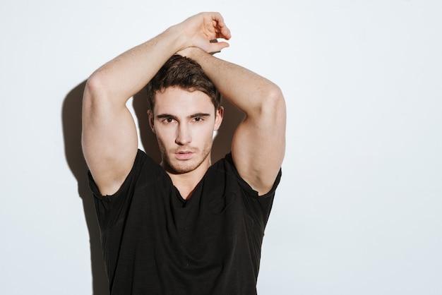 Foto van een sterke jonge man gekleed in een zwart t-shirt die zich voordeed op een witte achtergrond die naar de camera kijkt.