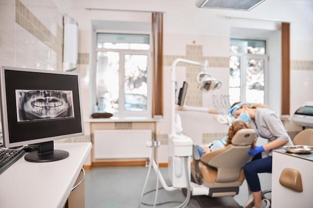 Foto van een tandartspraktijk met alle tandheelkundige apparatuur en toestellen en een grote röntgenfoto op het computerscherm