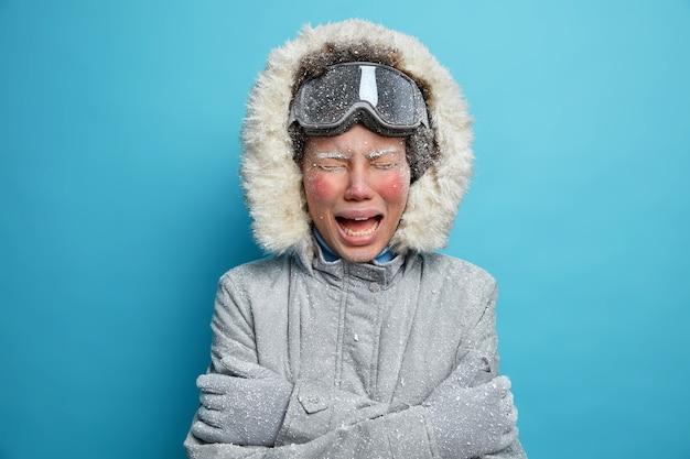 Foto van een teleurgestelde vrouw met een rood bevroren gezicht huilt als het voelt erg koud veel tijd buiten doorgebracht tijdens strenge ijzige winterdag draagt grijze bovenkleding trilt en knuffelt zichzelf. recreatie concept