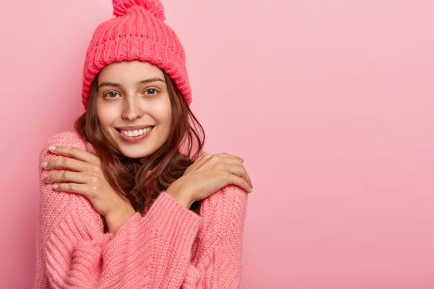 Foto van een tevreden lachende vrouw die warm is in een gebreide wintertrui, armen over de borst kruist en schouders raakt, heeft een aantrekkelijke uitstraling, poseert tegen een roze achtergrond, vrije ruimte opzij