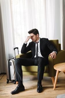Foto van een uitgeputte europese zakenman die een zwart pak draagt, zittend op een fauteuil met zijn ogen dicht in een hotelappartement