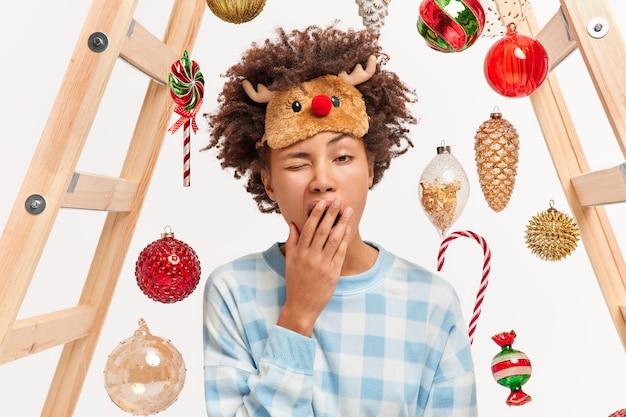 Foto van een uitgeputte vrouw wordt heel vroeg wakker in de ochtend gaapt en wil slapen heeft veel te doen voor het nieuwe jaar, gekleed in een geruite pyjama en een slaapmasker siert huis met kerstballen