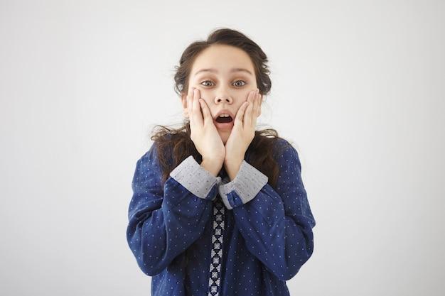 Foto van een verbaasd gefascineerd meisje met donker haar dat de mond wijd openzet, de handen op haar wangen vasthoudt, volledig ongeloof en geschokt uitdrukt en onverwacht verbazingwekkend nieuws ontvangt. echte emoties