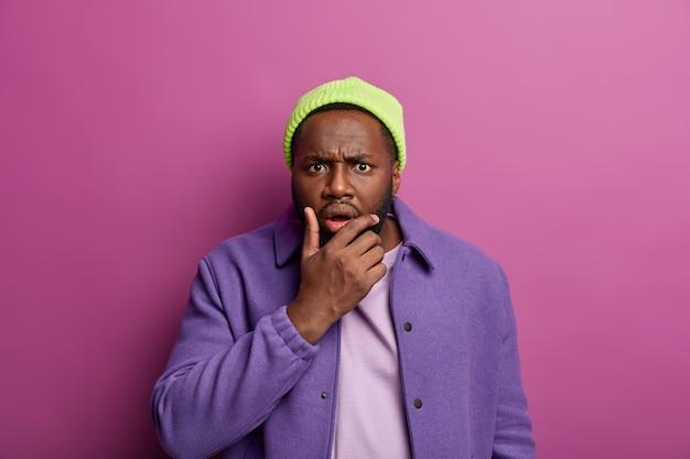 Foto van een verbaasde man met een boze geschokte uitdrukking, kin vasthoudt en met verbijstering naar de camera kijkt, kan iemands wrede acties niet begrijpen, draagt stijlvolle hoed