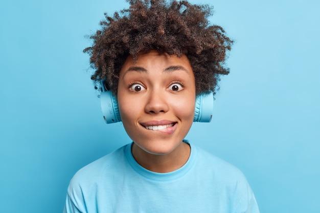 Foto van een verbaasde nieuwsgierige afro-amerikaanse vrouw die op de lippen bijt, ziet er direct uit met een draadloze koptelefoon gekleed in een casual t-shirt dat over een blauwe muur is geïsoleerd. mensen vrije tijd levensstijl