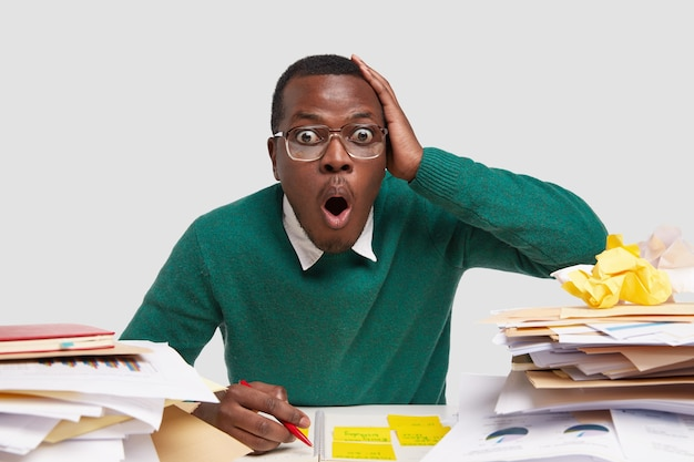 Foto van een verbaasde zwarte man houdt hand op het hoofd, mond open, draagt een grote bril, schrijft notities in kladblok