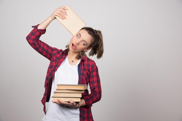 Foto van een vermoeide jonge student die een stapel boeken vasthoudt.