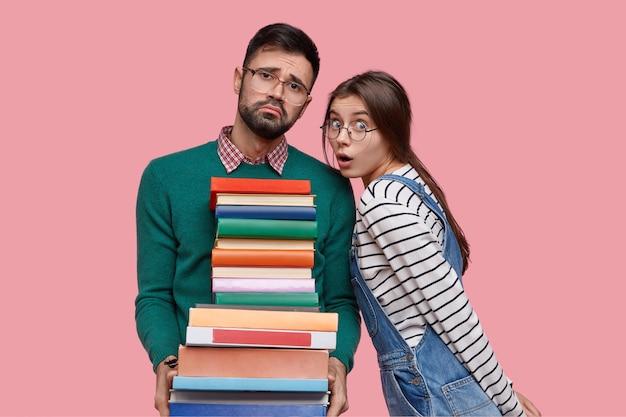 Foto van een vermoeide ongeschoren man met een uitdrukking van medelijden, houdt stapel boeken vast, kijkt ongenoegen, zijn vrouwelijke klasgenoot heeft een verbijsterde blik
