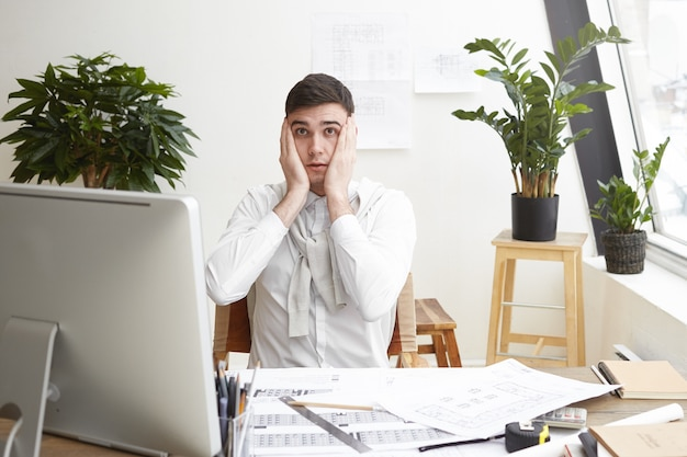 Foto van een verwarde, geschokte jonge mannelijke ontwerper of architect die op kantoor werkt, zich gestrest en nerveus voelt, de handen op zijn hoofd houdt, naar het computerscherm staart, fouten opmerkt in zijn tekeningen