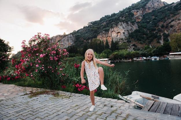 Foto van een vrij grappig opgewonden meisje bij de rivier in een witte zomerjurk.
