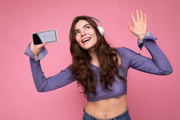 Foto van een vrij positieve jonge brunette met krullend haar in een paarse crop top geïsoleerd over roze