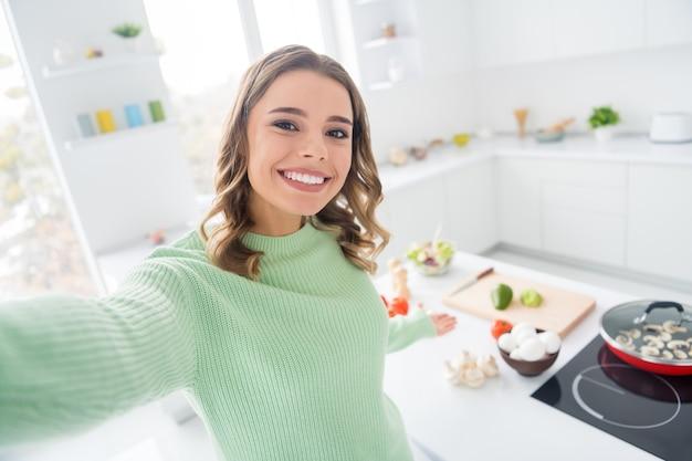 Foto van een vrij vrolijk meisje dat een smakelijke maaltijd kookt die je verwelkomt en selfie maakt
