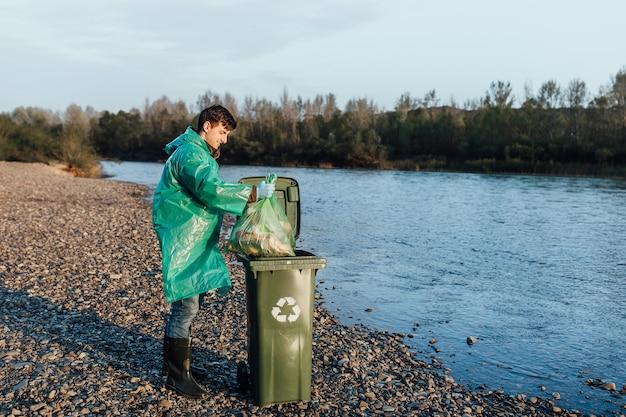 Foto van een vrijwilliger die afval in de buurt van de rivier schoonmaakt.