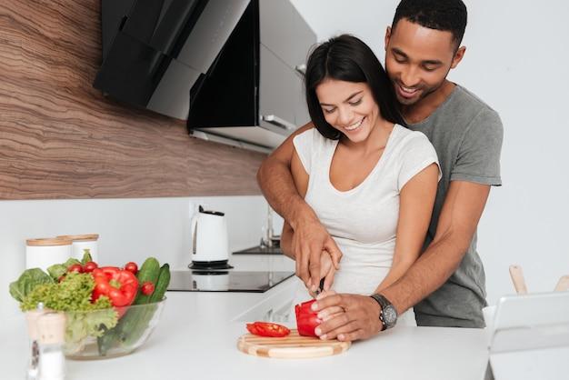 Foto van een vrolijk jong stel in de keuken knuffelen tijdens het koken.