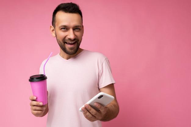 Foto van een vrolijk lachende knappe jonge ongeschoren brunette man met baard die elke dag lichtroze draagt