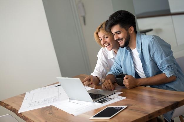 Foto van een vrolijk liefdevol jong stel dat een laptop gebruikt en hun financiën analyseert met documenten
