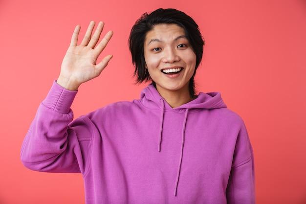 Foto van een vrolijke aziatische man met een sweatshirt die zich verheugt en zwaait op camera geïsoleerd over rode muur