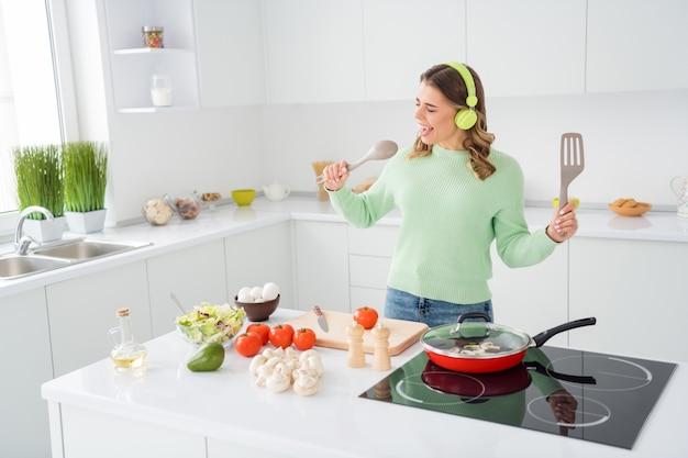 Foto van een vrolijke grappige dame die een smakelijk diner kookt en koptelefoonmuziek luistert