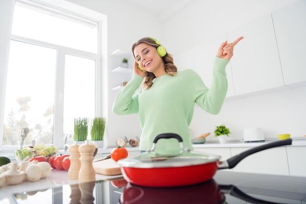 Foto van een vrolijke huisvrouw die een koptelefoon luistert, geniet ervan