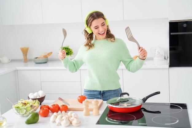 Foto van een vrolijke huisvrouw kijkt naar de koekenpan die de maaltijd controleert
