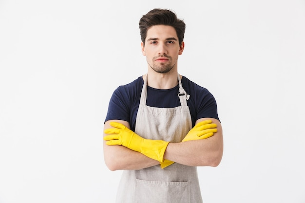 Foto van een vrolijke jonge man die gele rubberen handschoenen draagt ter bescherming van de handen, glimlachend tijdens het schoonmaken van het huis geïsoleerd over wit