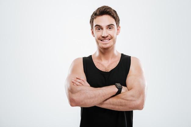 Foto van een vrolijke jongeman gekleed in een zwart t-shirt die over een witte muur staat met gekruiste armen en kijkend naar de camera.