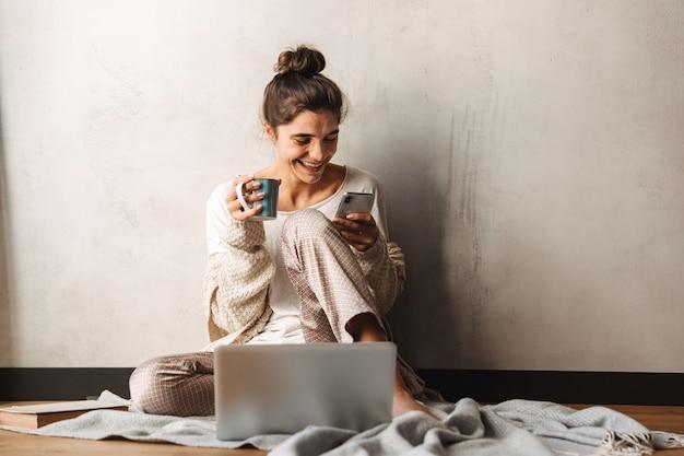 Foto van een vrolijke lachende vrouw die vrijetijdskleding draagt die koffie drinkt en een mobiele telefoon gebruikt terwijl ze thuis op de vloer zit