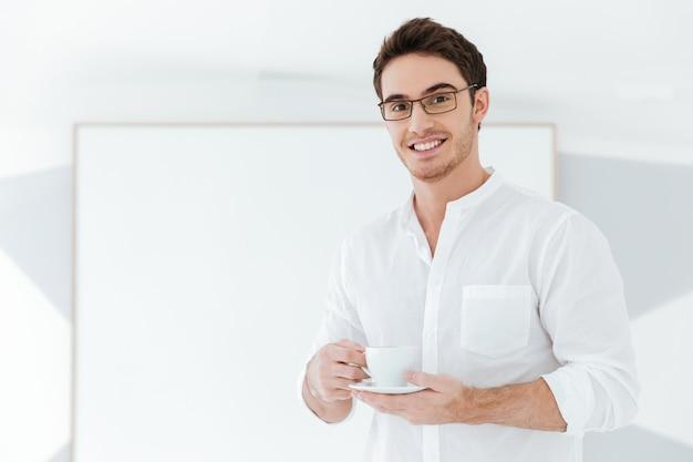 Foto van een vrolijke man met een bril en gekleed in een wit overhemd met een kopje koffie in de buurt van een groot bord. kijk naar de camera.