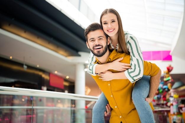Foto van een vrolijke, schattige dame, een knappe kerel, een verliefd stel, een bezoek aan een winkelcentrum, een winkelcentrum, een goed humeur, een wandeling, meeliften, plezier hebben, spelen, een casual jeans, een shirt, een outfit dragen