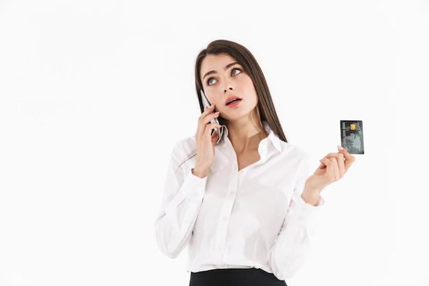 Foto van een vrolijke werkneemster, gekleed in formele kleding met smartphone en creditcard terwijl ze op kantoor werkt, geïsoleerd over een witte muur