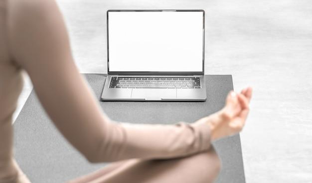 Foto van een vrouw die thuis online yoga beoefent met een laptop.