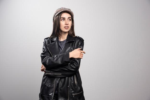 Foto van een vrouw die weg in zwart leerjasje en glb kijkt.