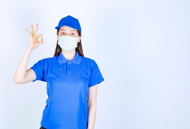 Foto van een vrouw in uniform die een medisch masker draagt en een goed gebaar toont.