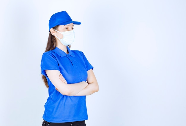 Foto van een vrouw in uniform die een medisch masker draagt en poseert met gekruiste armen.