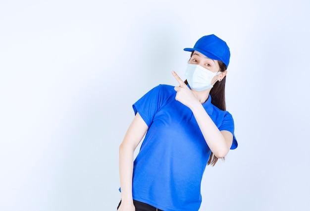 Foto van een vrouw in uniform en medisch masker die naar boven wijst.